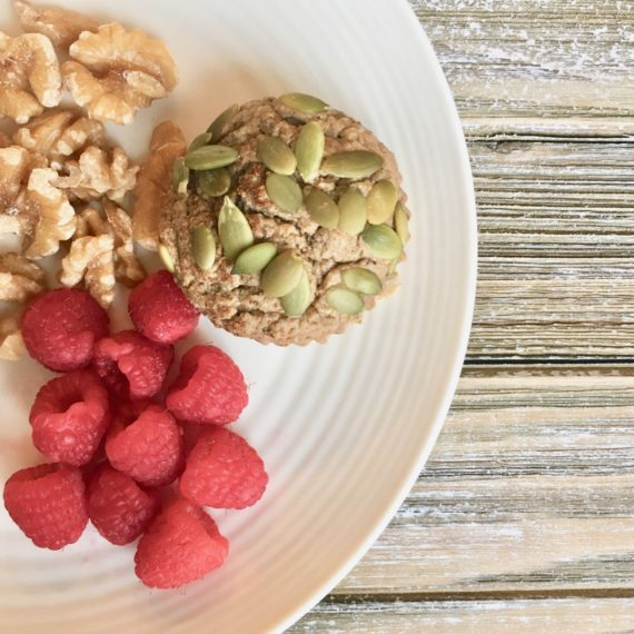 photo of a white plate with a muffin, raspberries, and walnuts on a wood table
